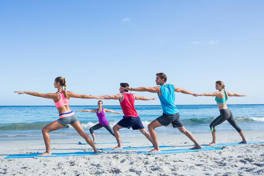 Friends doing yoga on the beach