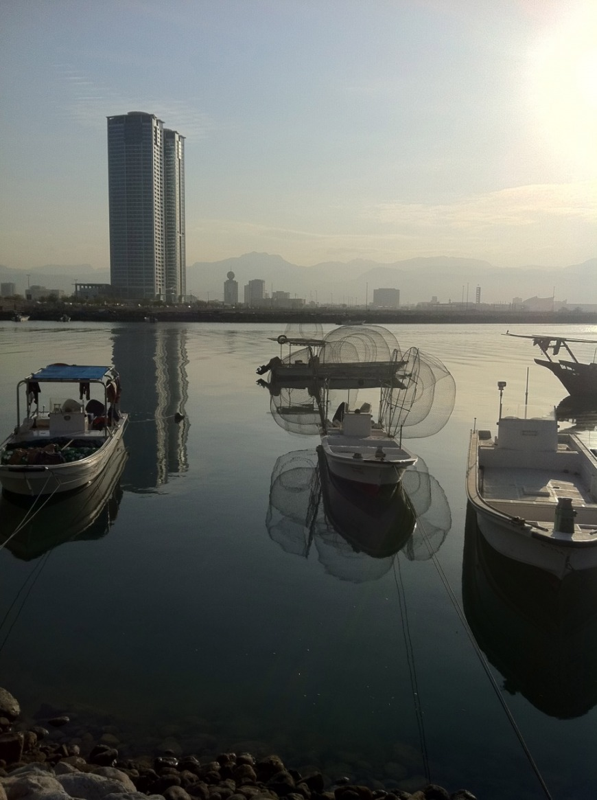 Fishing boats and Julfar Towers on the Creek
